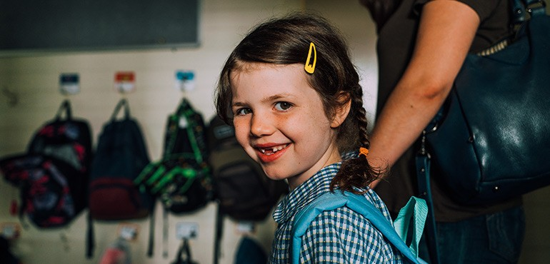 Little girl grins at the camera on her first day of school.